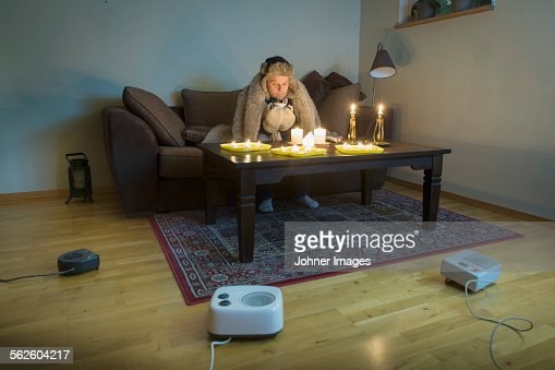 Man Sitting In Cold Living Room Stock Photo