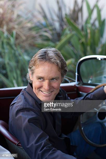 Man sitting in convertible car smiling over his shoulder
