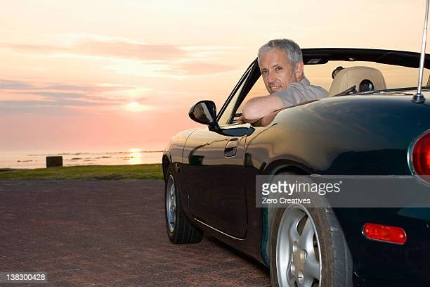 Man sitting in convertible on coastline