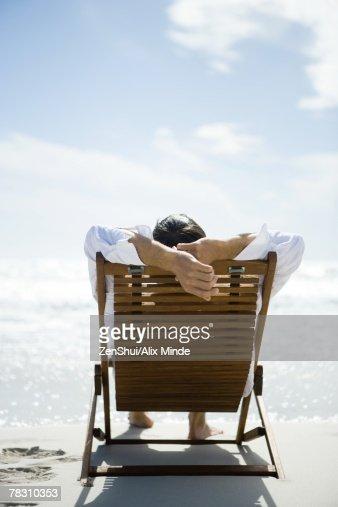 Man sitting in deck chair, facing sea, rear view