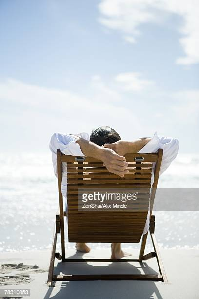 Man sitting in deck chair, facing sea, rear view