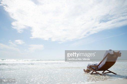 Man sitting in deckchair on beach, surf washing under him, rear view