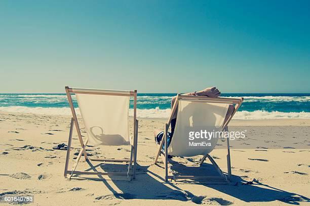 Man sitting in deckchair on the beach, Aveiro, Baixo Vouga, Portugal