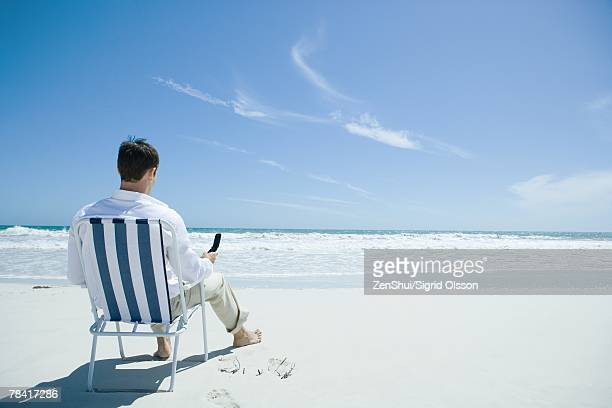 Man sitting in folding chair on beach, holding cell phone, rear view