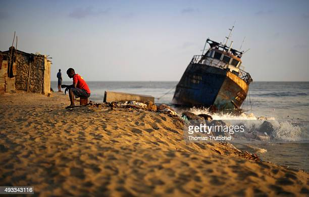 A man sitting in front of an old boat in the evening sun on the beach on September 28 2015 in Beira Mozambique