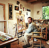 Man sitting in front of easel in art sudio, side view