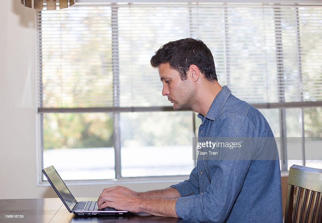 Man sitting in front of laptop by the window : Stock Photo