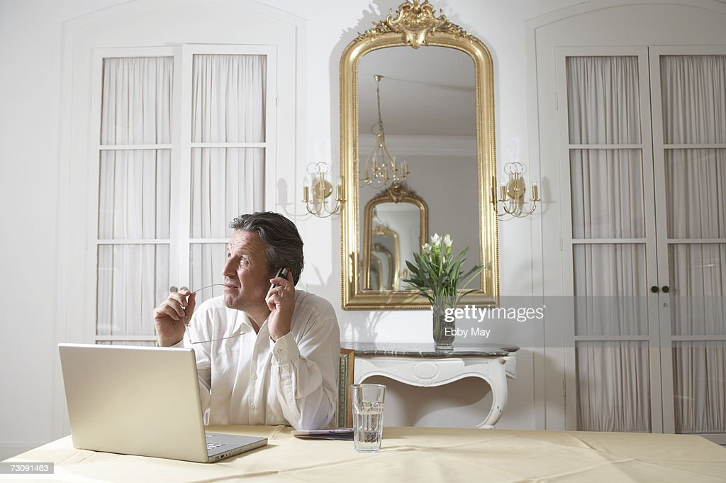 Man sitting in front of laptop, talking on mobile phone in opulent interior : Stock Photo