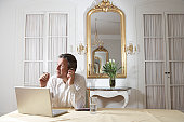 Man sitting in front of laptop, talking on mobile phone in opulent interior