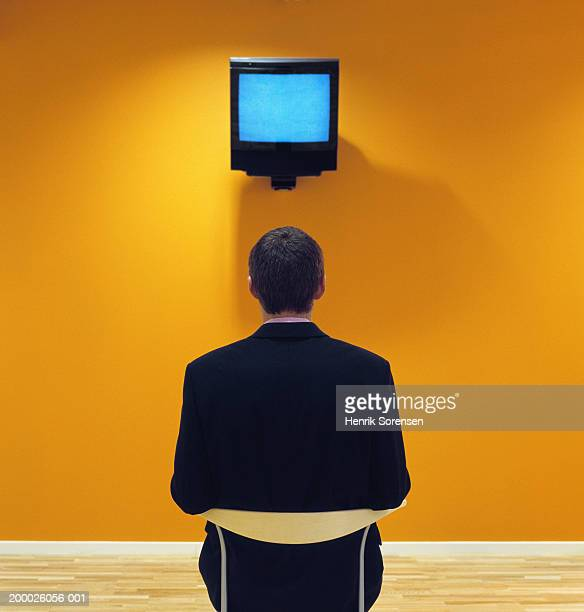 Man sitting in front of television mounted on wall, rear view