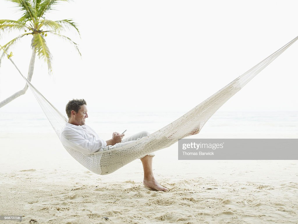 Man sitting in hammock on beach looking at palmtop