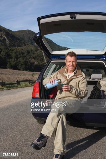 Man sitting in hatchback, pouring coffee