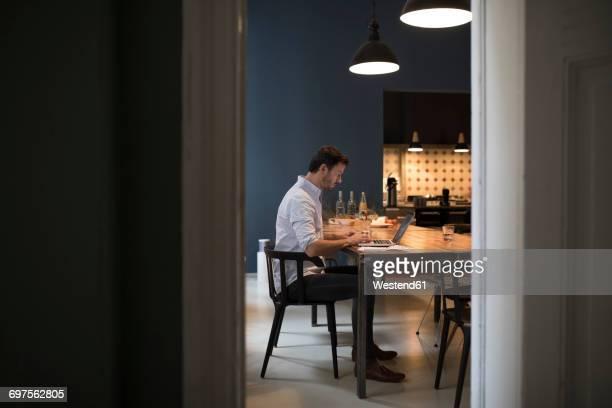 Man sitting in his living kitchen using laptop