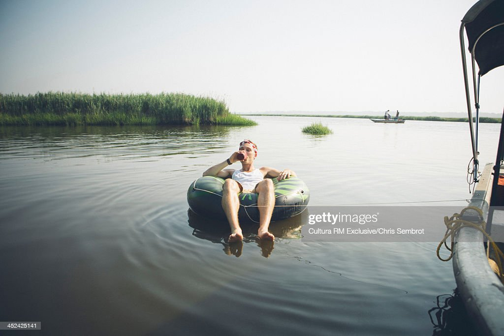 Man sitting in inflatable ring in river, drinking