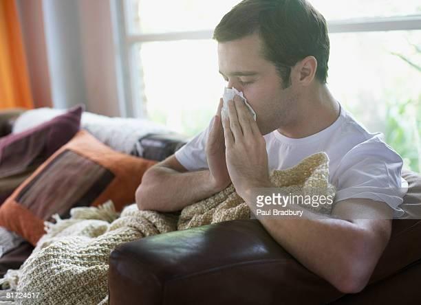 Mann sitzt im Wohnzimmer Schnäuzen