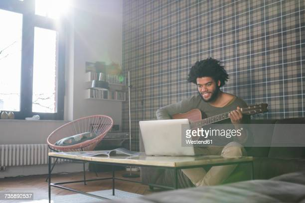 Man sitting in living room on sofa playing guitar in front of laptop