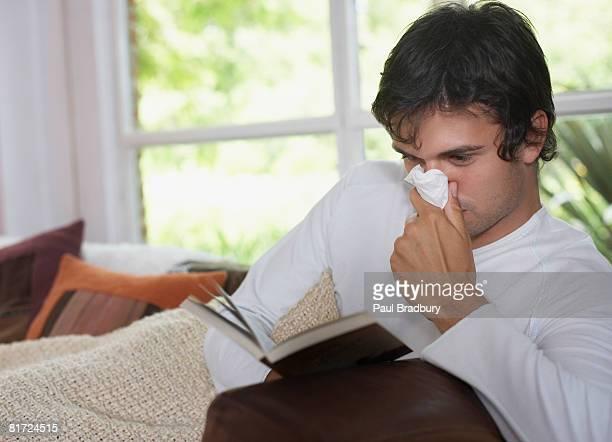 Mann sitzt im Wohnzimmer lesen Buch und Schnäuzen