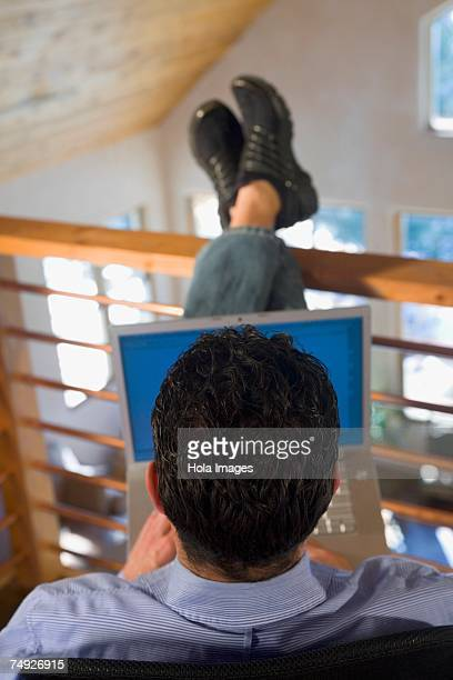 Man sitting in loft using laptop