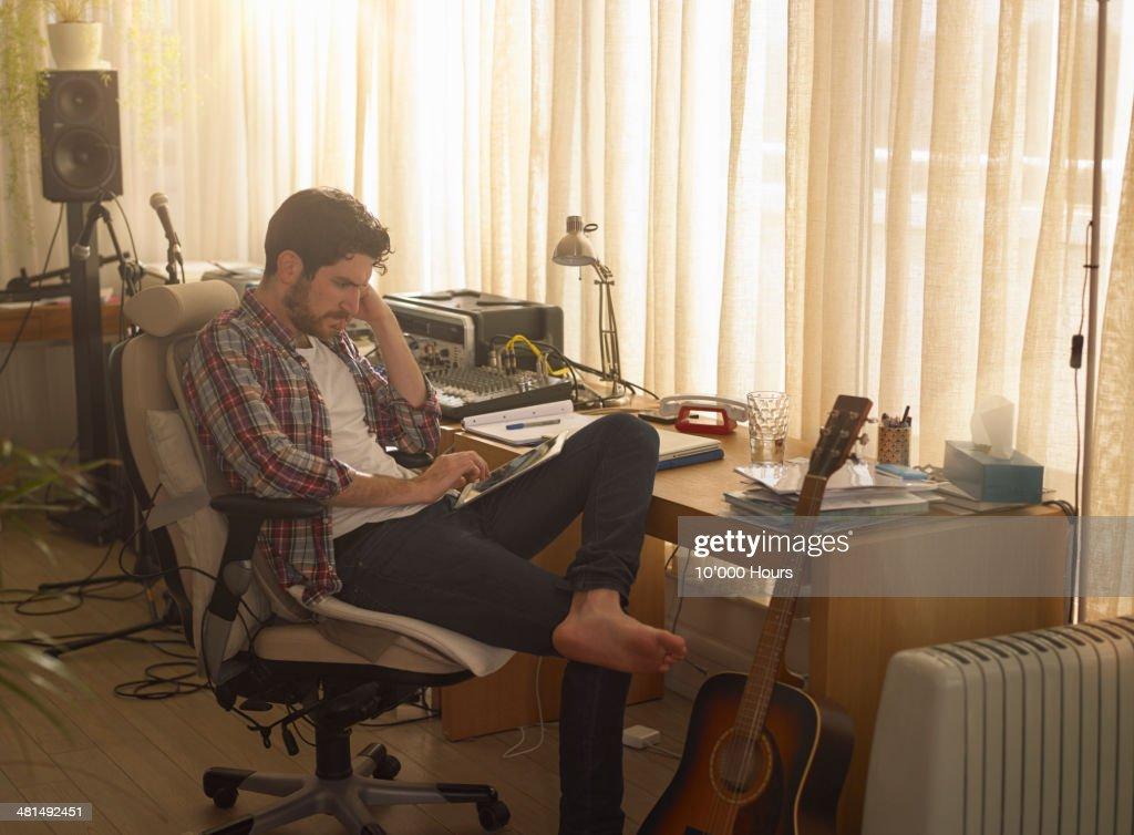 Man sitting in music studio using tablet computer