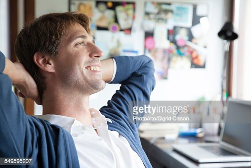 Man sitting in office daydreaming