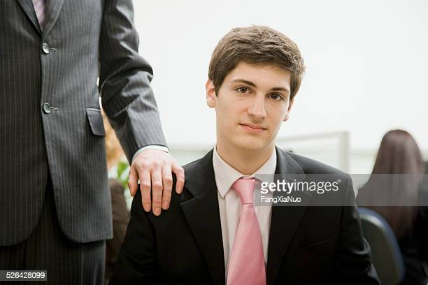 Man sitting in Office With Boss Behind Him