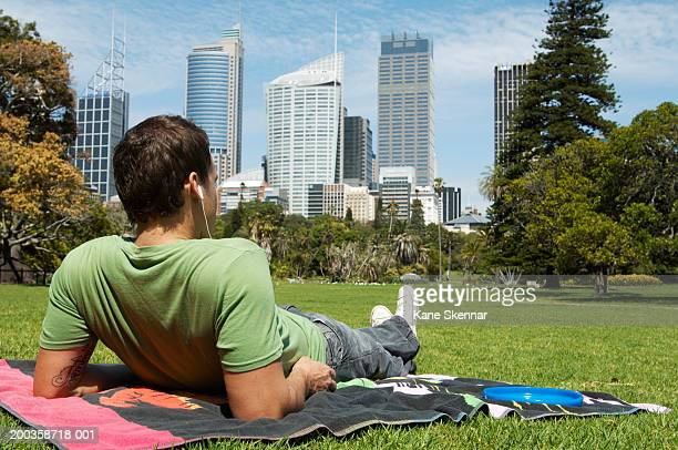 Man sitting in park listening to earphones