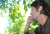Man sitting in park staring into distance