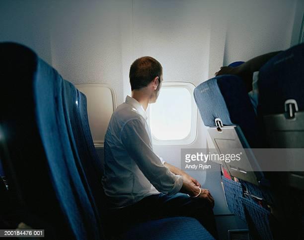 Man sitting in passenger plane, looking through window, side view