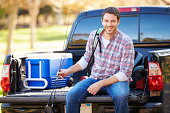 Man Sitting In Pick Up Truck On Camping Holiday Smiling To Camera Holding A Fishing Rod