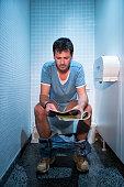man sitting in public restroom