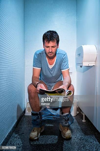 Mann sitzt in Öffentliche Toilette