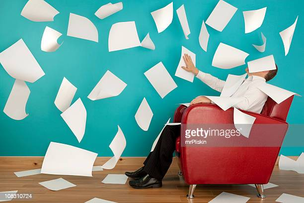 Man sitting in red chair with papers flying all around him
