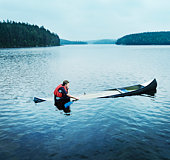 Man sitting in sinking kayak, side view