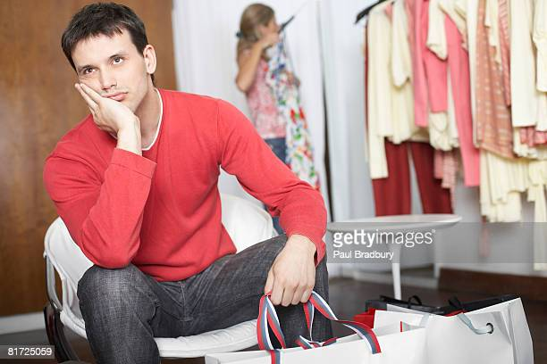 Man sitting in store waiting and looking bored