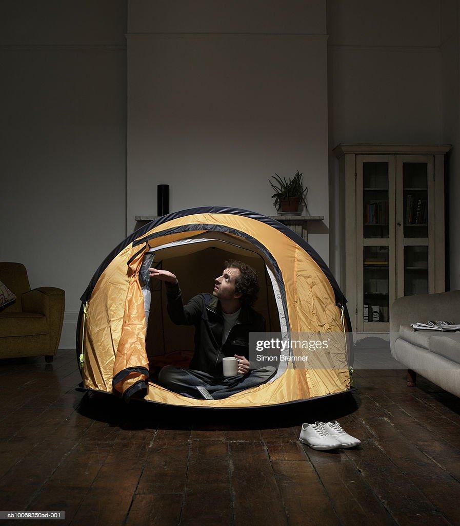 Mann Sitzen Im Zelt Im Wohnzimmer Stock Foto Getty Images