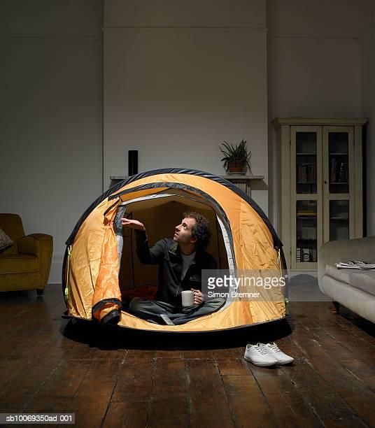 Homme assis dans une tente dans la salle de séjour