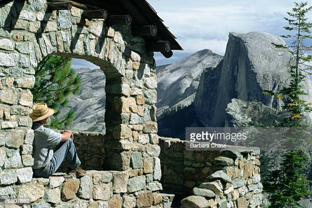 Man sitting in window with view of Half Dome, Yosemite National Park, California, USA