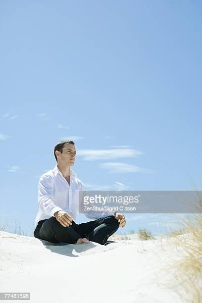 Man sitting indian style on dune