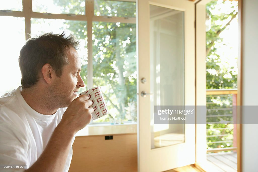 Man sitting indoors, drinking cup of coffee, side view : Stock Photo