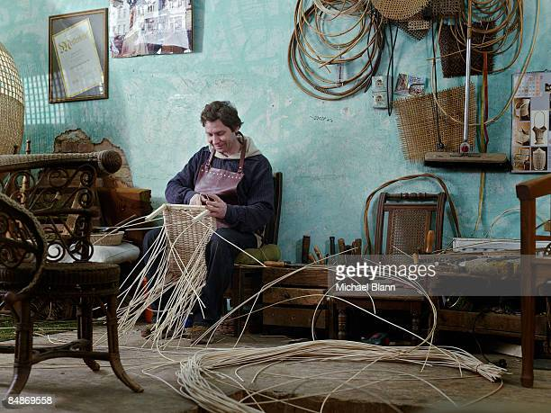 man sitting making a chair in a shop