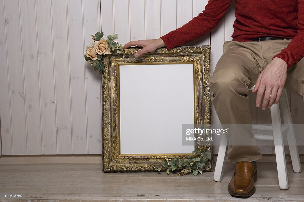 Man sitting next to picture frame : Stock Photo
