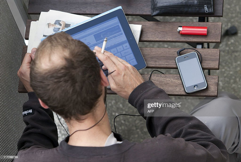 A man sitting on a balcony surfs the web on an iPad while listening to music on his iPhone in Berlin on June 23, 2011.
