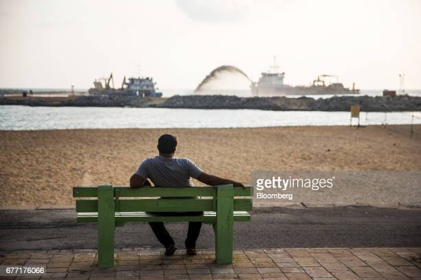 A man sitting on a bench at the sea front of Galle Face Green looks out towards a dredging vessel operating at the construction site of the Colombo...