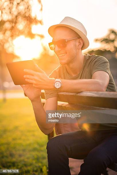 Man sitting on a bench reading on a tablet