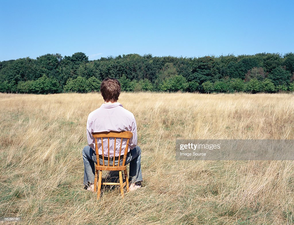 Man sitting on a chair in a field : Stock Photo