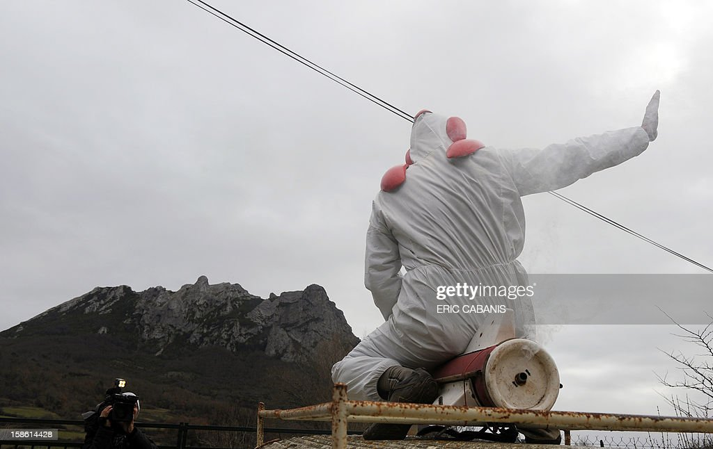 A man sitting on a fake rocket set on the roof of his car pretends taking off 1,231 meter high peak of Bugarach - one of the few places on Earth some believe will be spared when the world allegedly ends today according to claims regarding the ancient Mayan calendarto the dressed up as the Death walks, on December 21, 2012 in the French southwestern village of Bugarach. French authorities have pleaded with New Age fanatics, sightseers and media crews not to converge on the tiny village. AFP PHOTO / ERIC CABANIS