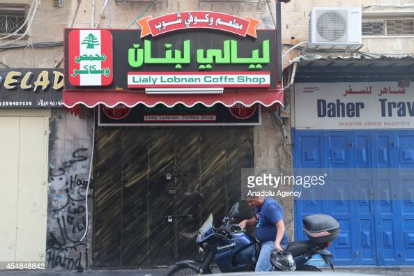 A man sitting on a motorcycle is seen next to shuttered stores during a strike which refers death of 16 years old Palestinian named Muhammed...