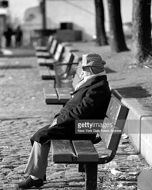 Man sitting on a park bench soaking up the sun on Greenpoint Avenue in Sunnyside Queens