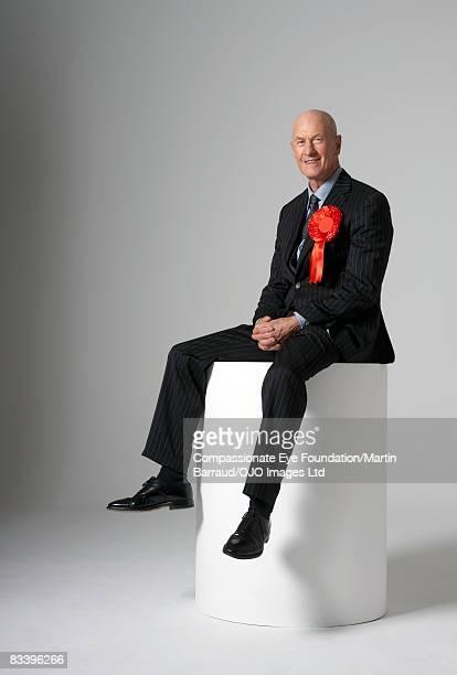 Man sitting on a pedestal, wearing a red ribbon