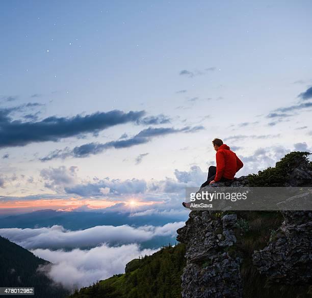 男に座るロックしながらクラウディ山の景色